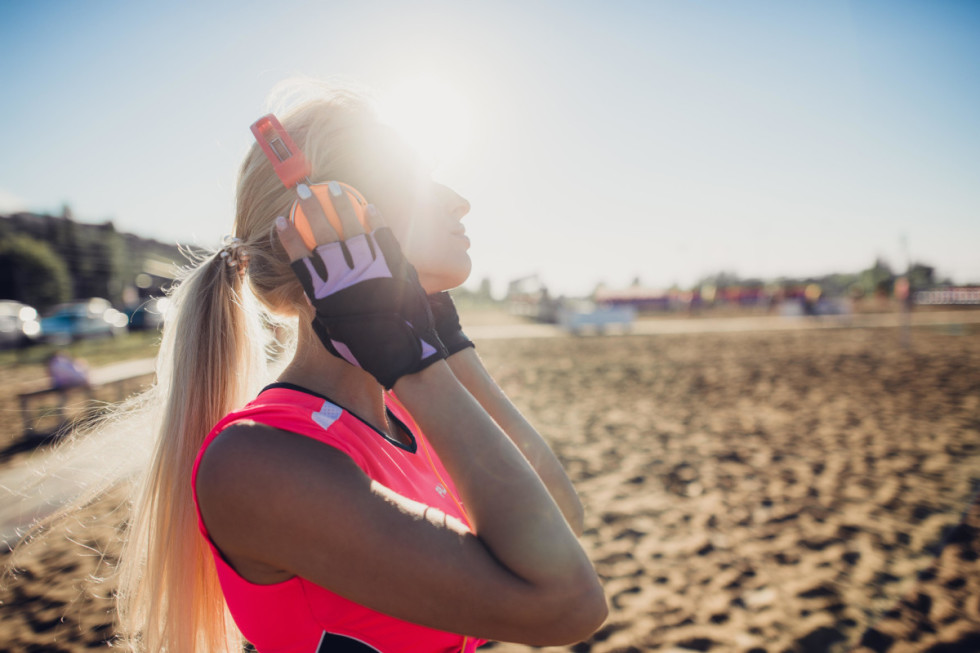 sport outdoor photo of beautiful young blonde woman in pink colorful sport suit listening to music on headphones by the beach.